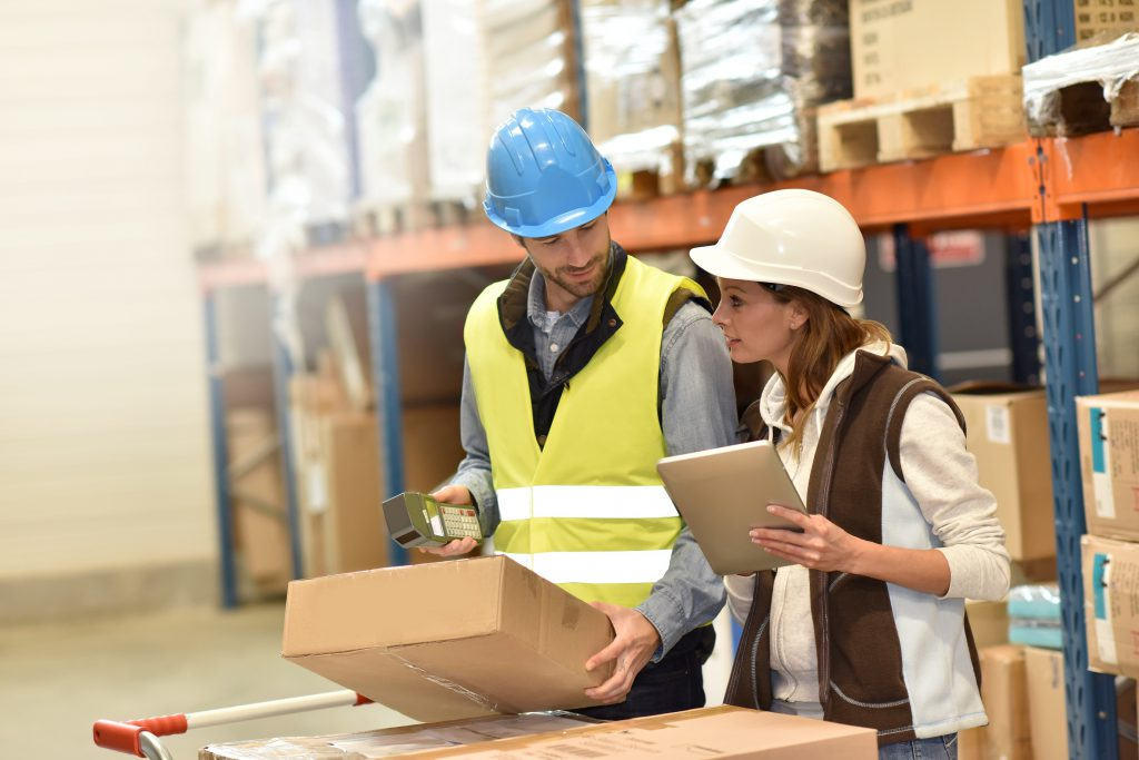 two managers of warehouse services with packages and clipboards