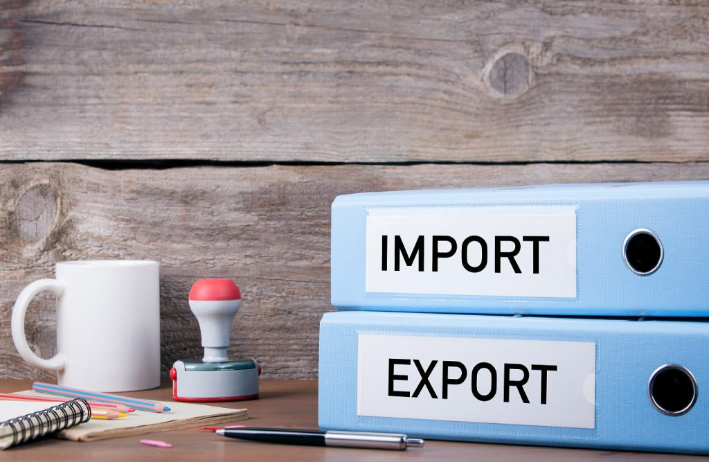 "Binders on a import and export company desk, labeled ""import"" and ""export"" respectively"