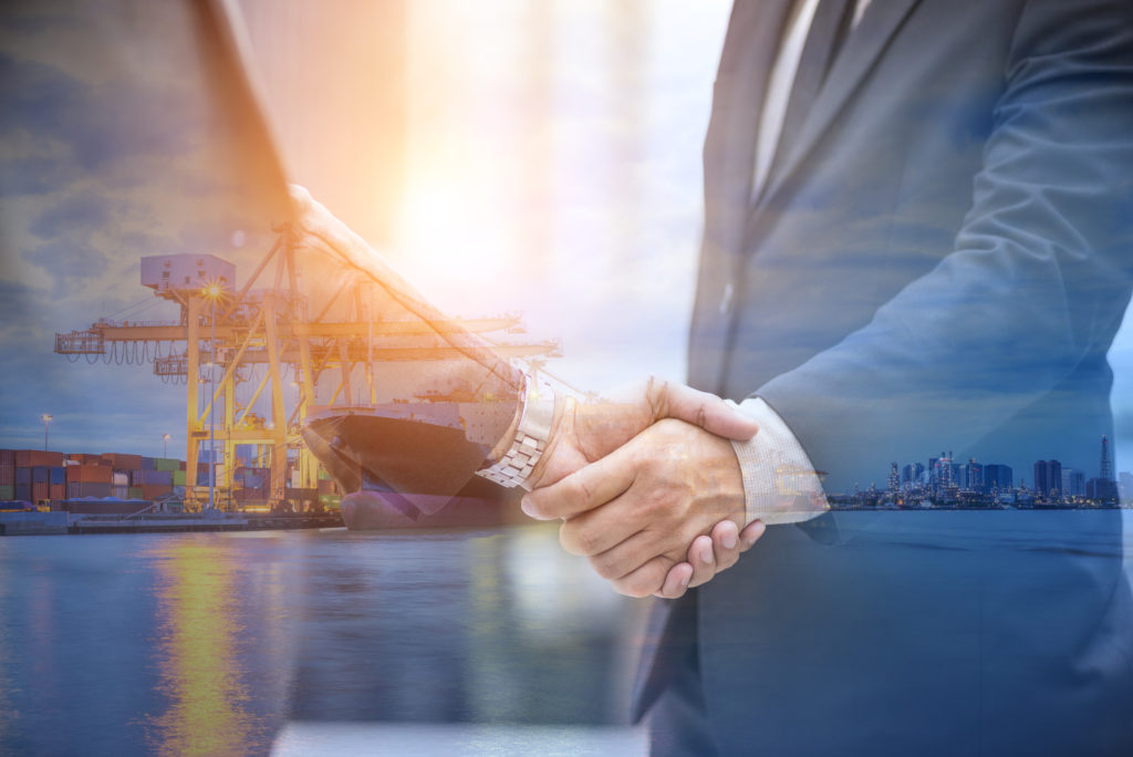 two businessmen shaking hands with a shipping yard in the background