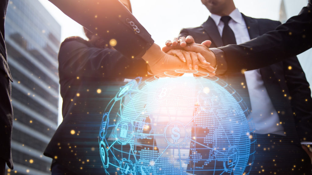 Close up of businessmen shaking hands. Global network and a world map in the foreground. block chain concept.